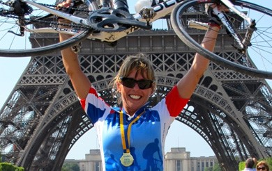 Female cyclist holing a bike above her head, with a medal around her neck, in front of the Eifel Tower