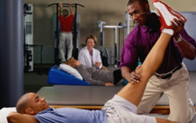 A physiotherapist performs leg stretches on a male patient who is lying on a physio bed