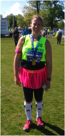 Jo Eaton stands at the finish of the Edinburgh Marathon with her winner's medal around her neck