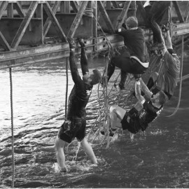 Participants climb from water onto an iron girder bridge in the obstacle race