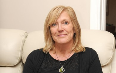 Mel Lightfoot sitting on her sofa. Mel has blonde shoulder-length hair and is wearing a black top with a pendant around her neck.