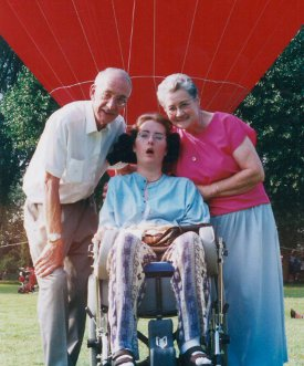 Alison Robins (centre) sitting in a wheelchair with her parents Joan and Ken smiling on either side of her.