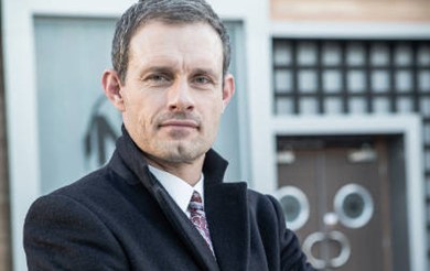 Coronation Street's Nick Tilsley, played by Ben Price, stands looking at the camera in front of Nick's Bistro.
