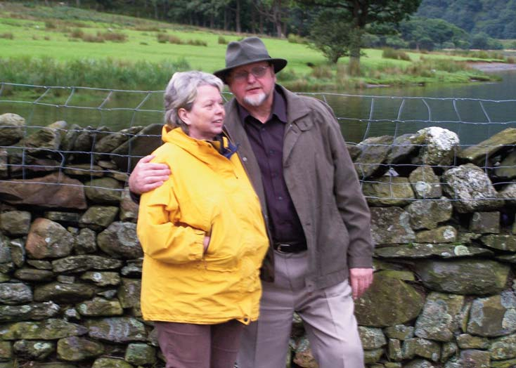 David and Janice Horner. David has his arm around Janice. The two are standing in front of a dry stone wall which walking in the countryside.