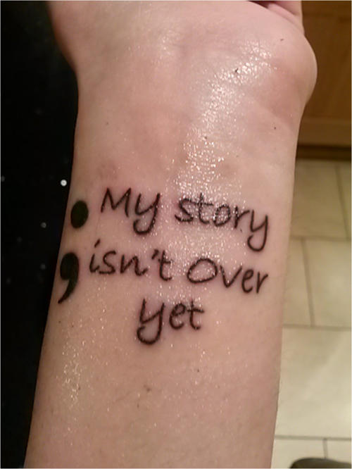 Anna's tattoo on her forearm - reads 'My story isn't over yet'