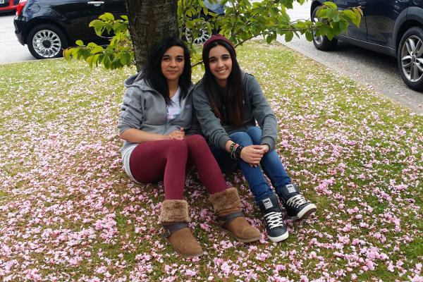 Anna Khan sitting on the grass underneath a tree with her twin sister
