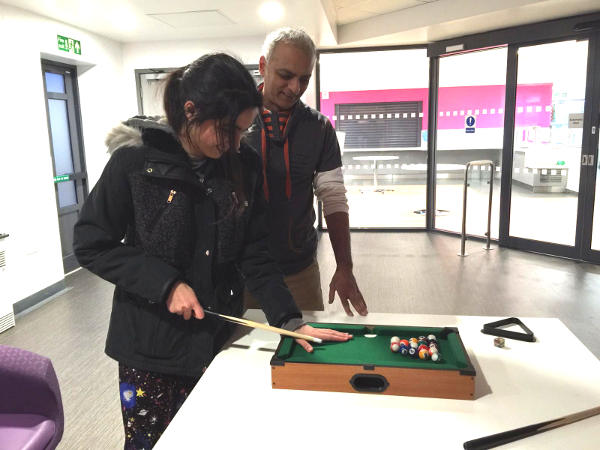Anna playing mini pool with her father, as part of her rehabilitation programme