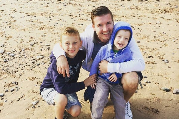 Mark Simcox, Eleanor's husband, on the beach with their two sons