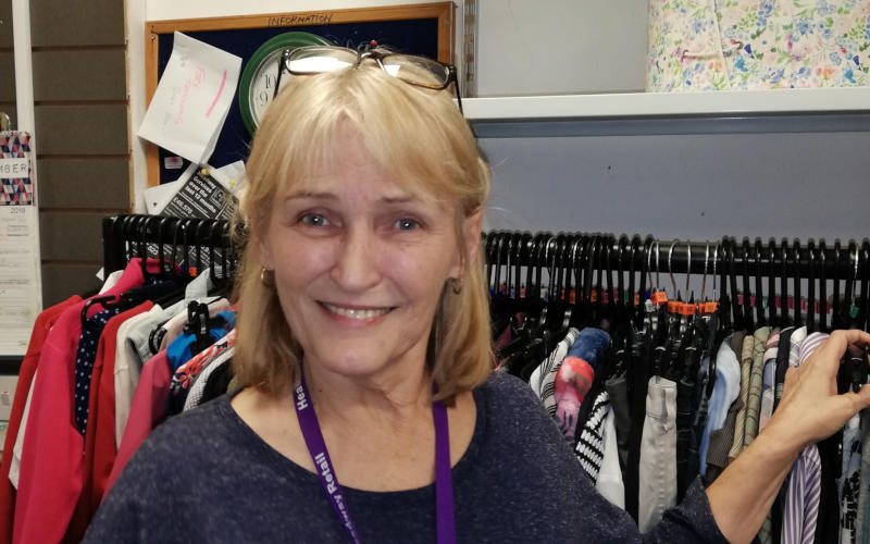 Jayne Copeman, Headway charity shop volunteer, stands smiling in front of a rail of clothes.