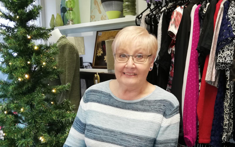 Headway charity shop volunteer Diane Noland, standing in front of a rail of clothes and the shop's Christmas tree