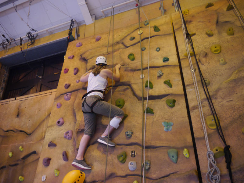 Adventurous Meg scales the climbing wall at Calvert Trust Lake District