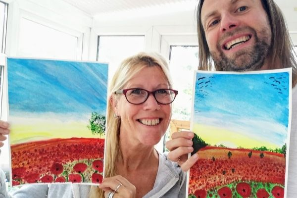Mark and Jules hold up some of their artworks