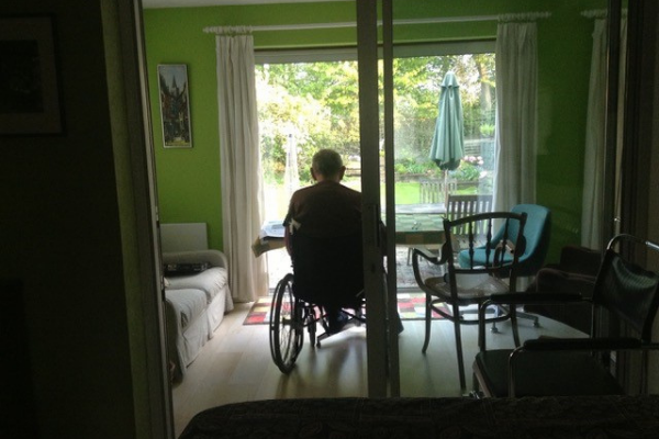 Terry Oliver sits in his wheelchair looking out at the garden outside.